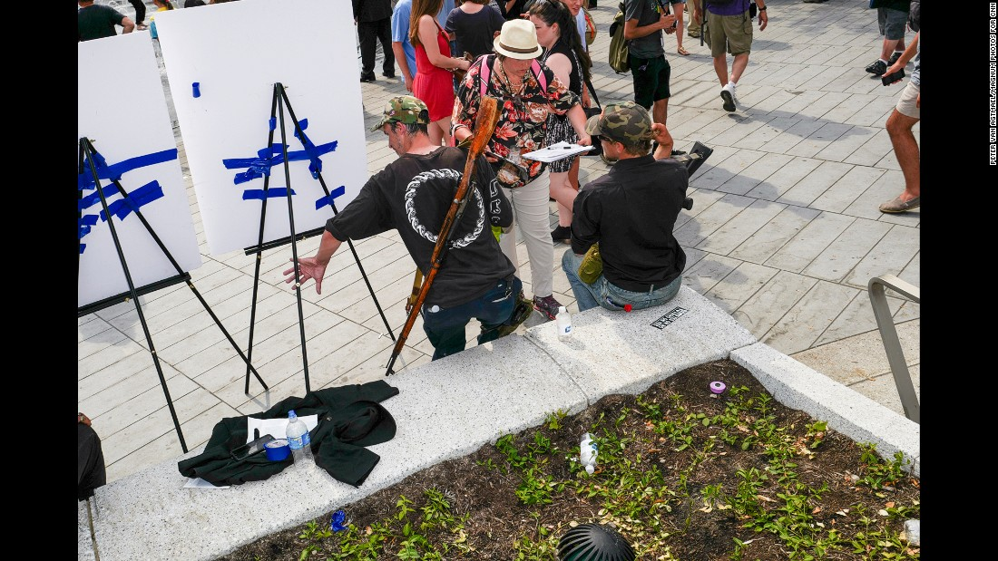 """Two men hold firearms in Cleveland's Public Square. """"I've seen open carry before but not quite in these numbers,"""" van Agtmael said."""