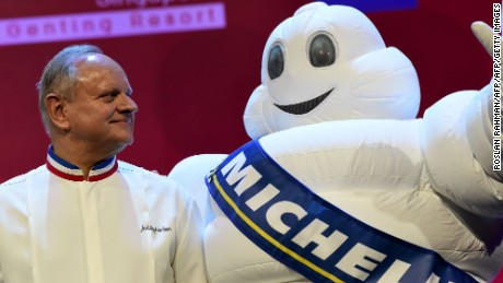Joel Robuchon, whose eponymous restaurant was awarded three Michelin stars poses with the tire company's mascot in Singapore.