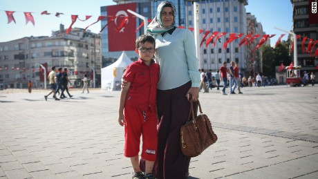 Nurdan, a housewife and mother, poses for a photo with her son, in Taksim Square, in Istanbul.
