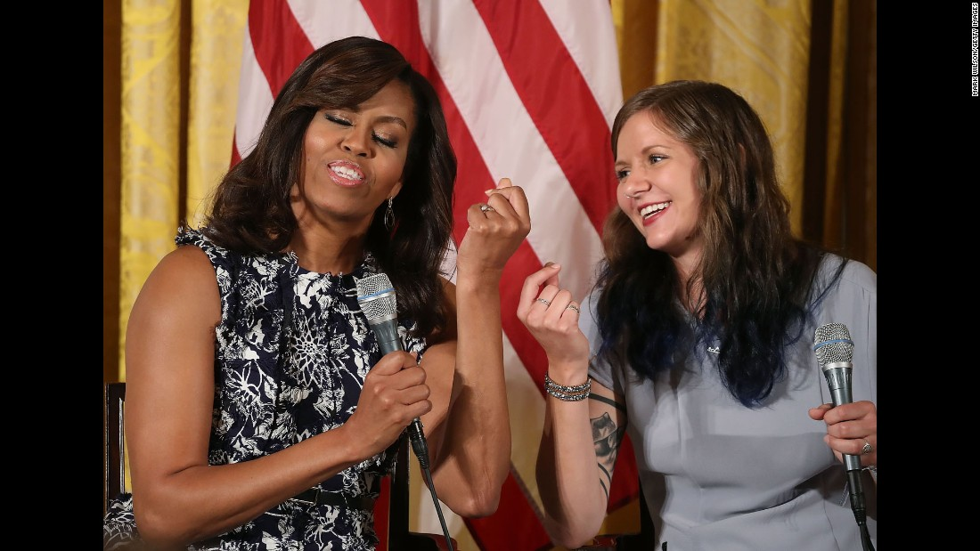 "First lady Michelle Obama snaps her fingers with student Rachel Scott at a White House event on Tuesday, July 19. The first lady was hosting the third-annual ""Beating the Odds"" summit with more than 130 college-bound students."