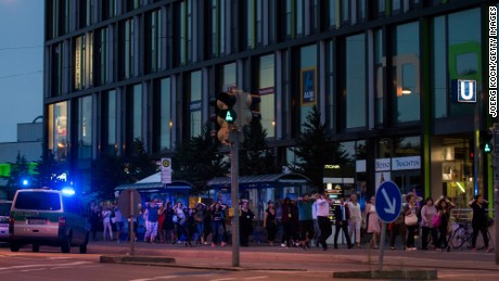 MUNICH, GERMANY - JULY 22:  Police officers escort people with their hands raised from inside the shopping center as they respond to a shooting at the Olympia Einkaufzentrum (OEZ) at July 22, 2016 in Munich, Germany.  According to reports, several people have been killed and an unknown number injured in a shooting at a shopping centre in the north-western Moosach district in Munich. Police are hunting the attacker or attackers who are thought to be still at large. (Photo by Joerg Koch/Getty Images)