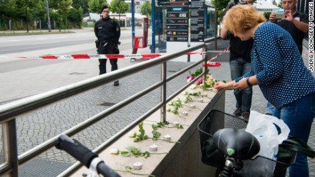 A woman lays nine flowers and nine candles outside the OEZ shopping center the day after a shooting spree left nine victims dead on Saturday July 23 in Munich, Germany.