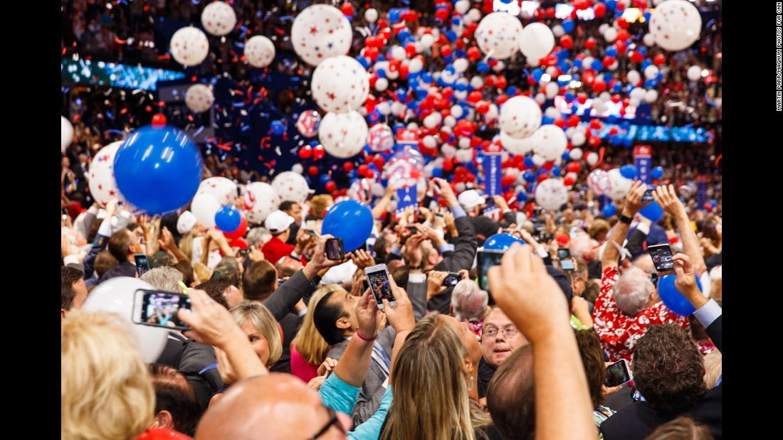 Delegates take photos and watch as balloons drop at the end of the convention.
