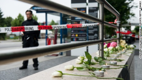 MUNICH, GERMANY - JULY 23: Nine flowers and nine candles layed by people outside the OEZ shopping center the day after a shooting spree left nine victims dead on July 23, 2016 in Munich, Germany. According to police an 18-year-old German man of Iranian descent shot nine people dead and wounded at least 16 before he shot himself in a nearby park. For hours during the spree and the following manhunt the city lay paralyzed as police ordered people to stay off the streets. Original reports of up to three attackers seem to have been unfounded. The shooter's motive is so far unclear. (Photo by Joerg Koch/Getty Images)