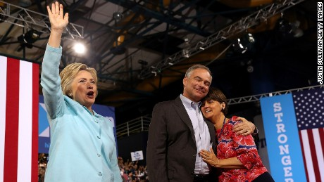 Hillary Clinton (L) greets suporters as democratic vice presidential candidate U.S. Sen. Tim Kaine (D-VA) hugs his wife Anne Holton during a campaign rally at Florida International University Panther Arena on July 23, 2016 in Miami, Florida.
