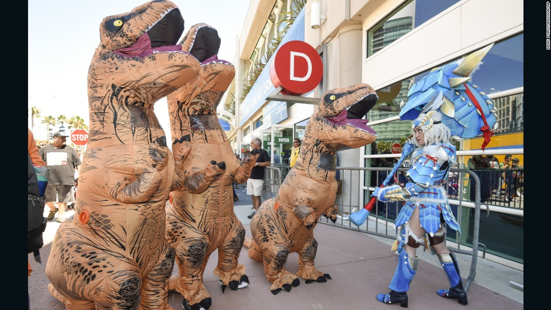 Katherine Masiewicz, dressed as a monster hunter, faces off against a group of dinosaurs as they pose for photographers outside the convention center.