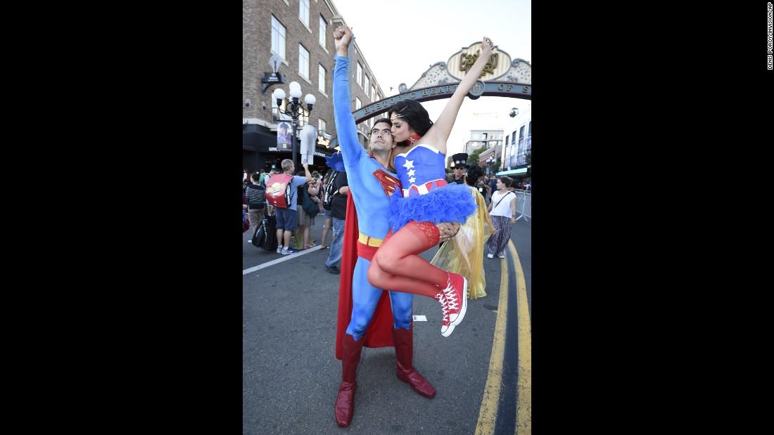Sergio Valente, as Superman, lifts Jessica Randall, as Vixen, as she gives him a kiss.
