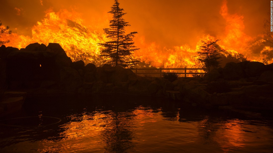 Flames from the Sand Fire are reflected in a backyard swimming pool on Saturday in Santa Clarita.<br />