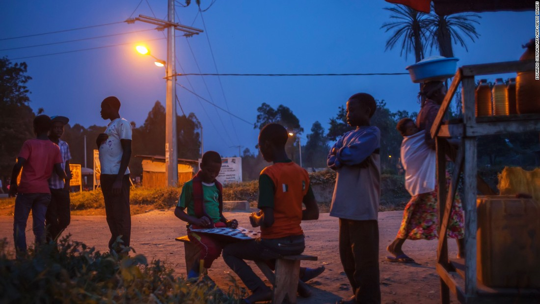 People socialize in the streets enlightened by electric lightning in the town of Bugara, powered by the Matebe facility. The vast majority of the Congolese population doesn't have access to electricity.