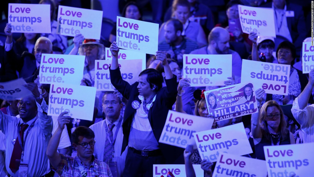 "Delegates hold signs reading ""Love trumps hate"" on Monday."