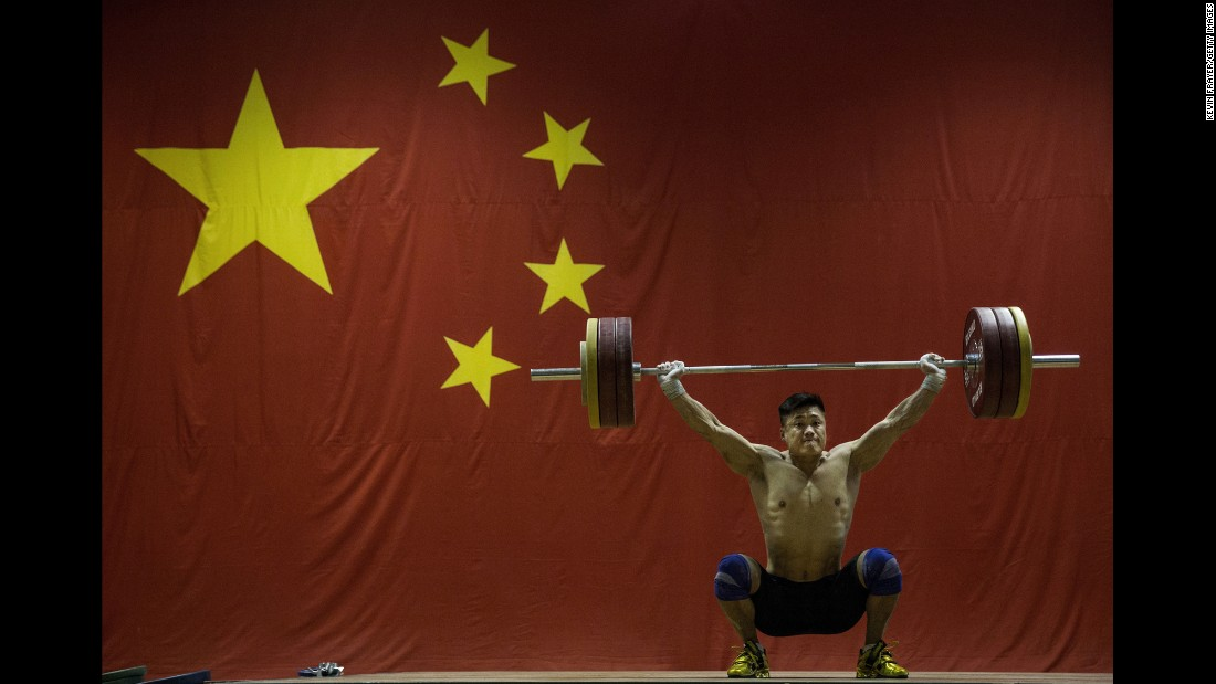 Chinese weightlifter Lu Xiaojun trains in Beijing on Friday, July 22. He won Olympic gold four years ago.