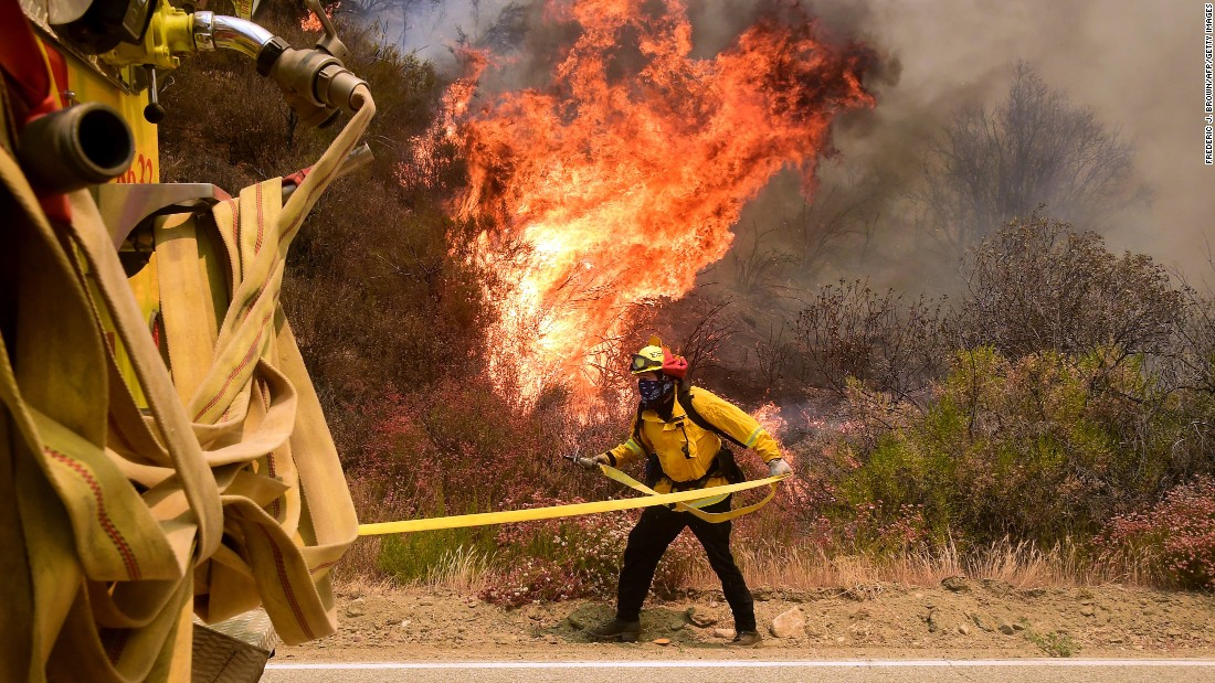 A fireman grabs his hose to battle a fire off Placerita Canyon Road in Santa Clarita.