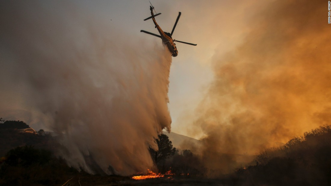 A helicopter makes a drop on a wildfire near Placerita Canyon Road in Santa Clarita on Sunday.