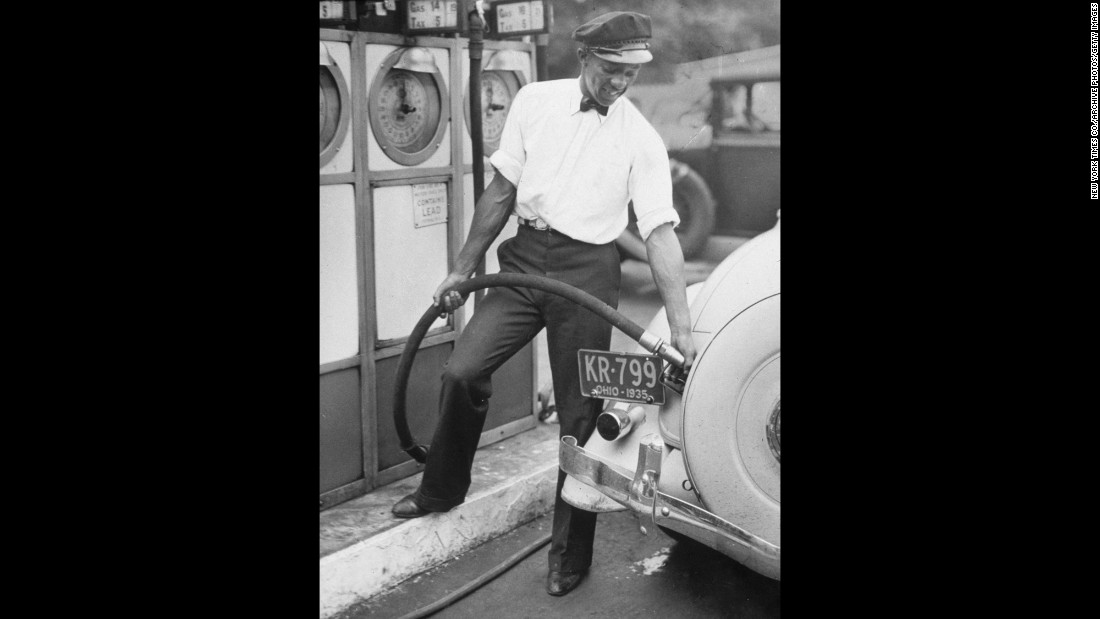 Owens fills up a car with gas in July 1935. He worked as a gas-station attendant to help pay for his college.