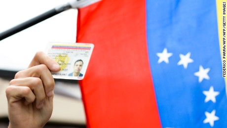 A Venezuelan shows his ID card during a spontaneous demonstration after the closure of centres to authenticate their signatures for a recall referendum against Venezuelan President Nicolas Maduro, in front of the National Electoral Council (CNE) in Caracas, on June 24, 2016.  Soaring crime, runaway inflation and a sharply contracting economy, worsened by falling oil prices, have fueled a drive for a recall referendum to remove Maduro, as a way out of the crisis. / AFP / FEDERICO PARRA        (Photo credit should read FEDERICO PARRA/AFP/Getty Images)