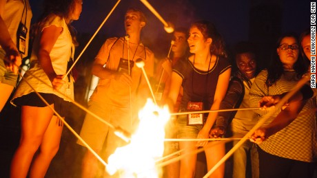Campers at the Tuesday's Child retreat roast marshmallows over a fire together.