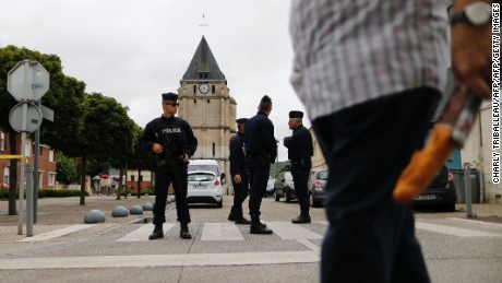 Police officers stand guard at the Saint-Etienne church.