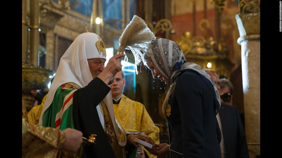 Russian Orthodox Church Patriarch Krill, left, blesses one of the athletes.