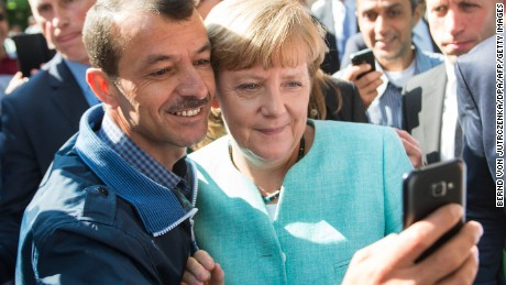 An asylum seeker takes a selfie with German Chancellor Angela Merkel in Berlin on September 10, 2015.