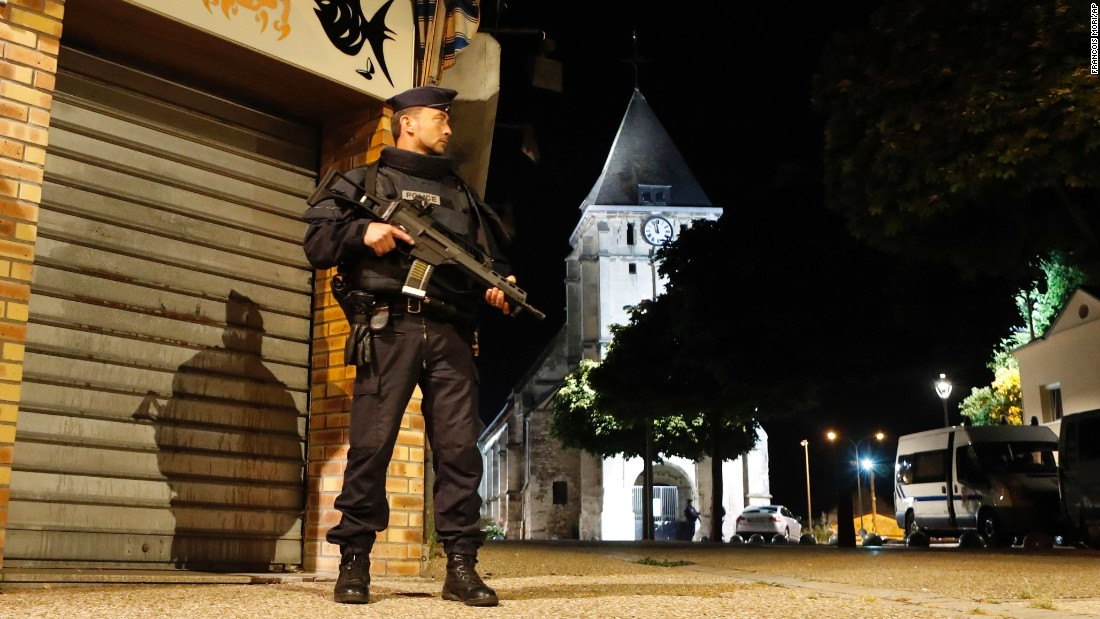 "A police officer guards a street in the French town of Saint-Etienne-du-Rouvray after an attack left a priest dead on Tuesday, July 26. French President Francois Hollande said <a href=""http://www.cnn.com/2016/07/26/europe/france-normandy-church-hostage/"" target=""_blank"">the attack</a> was a ""cowardly assassination"" carried out by two terrorists in the name of ISIS."