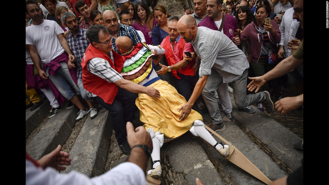 People help a dancer as he falls on his stilts during the traditional Los Zancos Dance in Anguiano, Spain, on Saturday, July 23.