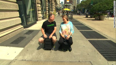 Now you can ride your suitcase. CNN's Jeanne Moos took a test drive on a motorized suitcase.      Why carry your luggage when it can carry you? Now you can ride your suitcase along those long airport hallways. Video of Modobag has gone viral and today I got to test drive a suitcase on NYC sidewalks. The bag is designed to fit as carryon. It has handlebars that pop up and foot holds that pop out. Very James Bond to convert it from luggage to a suitcase you can ride on. Top speed is 8 miles an hour and it handles well. The creator and I drove alongside one another discussing intricacies like ?how come no turn signals?? At least I didn?t mow anyone down driving my suitcase.