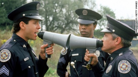 UNSPECIFIED - DECEMBER 31:  Medium shot of Steve Guttenberg as Mahoney and G.W. Bailey as Captain Harris both yelling at each other through megaphones while Michael Winslow as Jones and man look on; all wearing police uniforms and hats.  (Photo by Warner Bros./Getty Images)