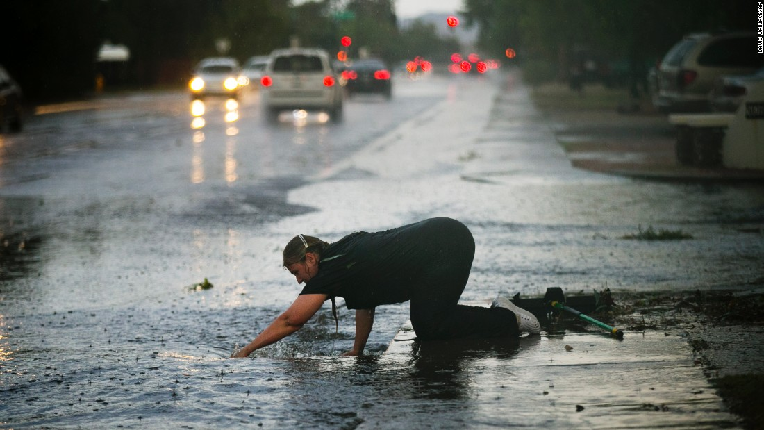 Silvia Graham removes debris from a storm drain in front of her Phoenix home after heavy rains on Monday, July 18.