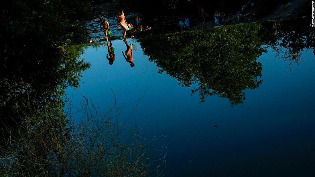 People in Pamplona, Spain, cool off in the Arga river on Tuesday, July 19.
