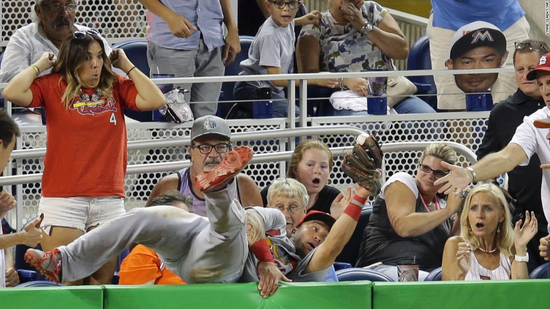 Kolten Wong, second baseman for the St. Louis Cardinals, dives into the stands to make a catch in Miami on Friday, July 29.