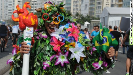 "A man disguised as Batman holds a fake Olympic torch reading ""Shame"" during a protest against suspended president Dilma Rousseff and former president Luiz Inacio Lula Da Silva, at Copacabana beach in Rio de Janeiro, Brazil, on July 31, 2016. Protesters took to the streets of Brazil on Sunday to demand the final leaving of suspended President Dilma Rousseff or to defend her continuance, just five days before the start of the Rio 2016 Olympic Games. / AFP / TASSO MARCELO        (Photo credit should read TASSO MARCELO/AFP/Getty Images)"