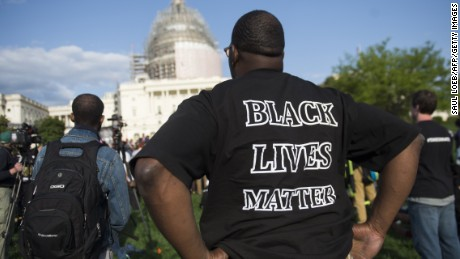 "A man wears a ""Black Lives Matter"" t-shirt as he demonstrates along with the group Justice League NYC and others participate in a March2Justice rally for criminal justice reform legislation to end racial profiling and demilitarize police forces outside the US Capitol in Washington, DC, April 21, 2015. Some members of the group spent a week traveling from New York City to Washington, ending with a protest rally on the National Mall. AFP PHOTO / SAUL LOEB        (Photo credit should read SAUL LOEB/AFP/Getty Images)"