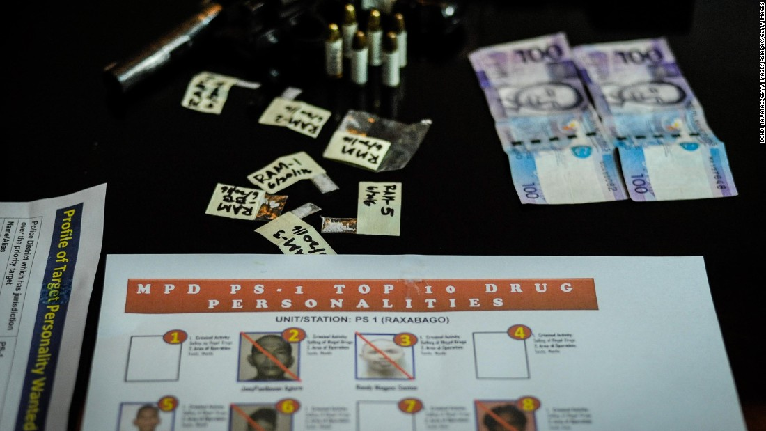 A gun, bullets, marked money and sachets of crystal meth are laid on a table after a drug raid  in Manila on June 20, 2016.