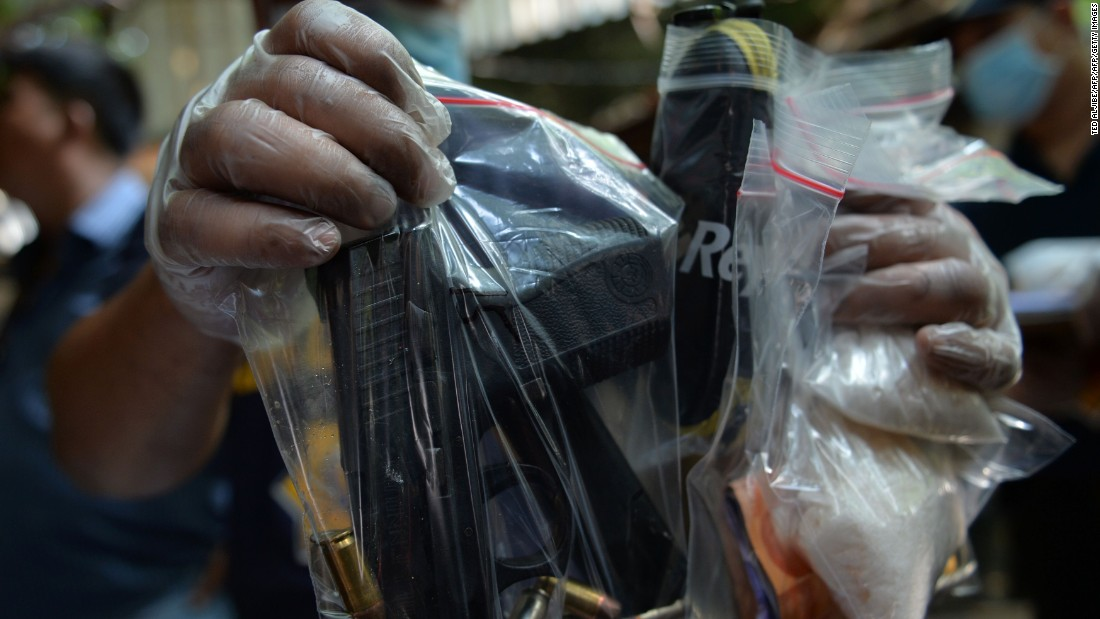 A Philippine police forensic investigator displays packets of drugs and a hand gun found inside a shanty where members of a suspected drug syndicate were killed after a shootout with police on July 3, 2016.
