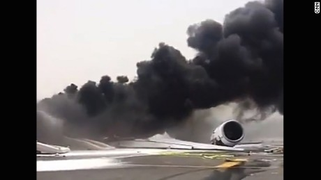 Dark smoke billows from the Emirates plane at Dubai International Airport.