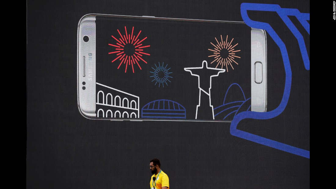A volunteer walks past an advertisement in Rio's Olympic Park on August 3.