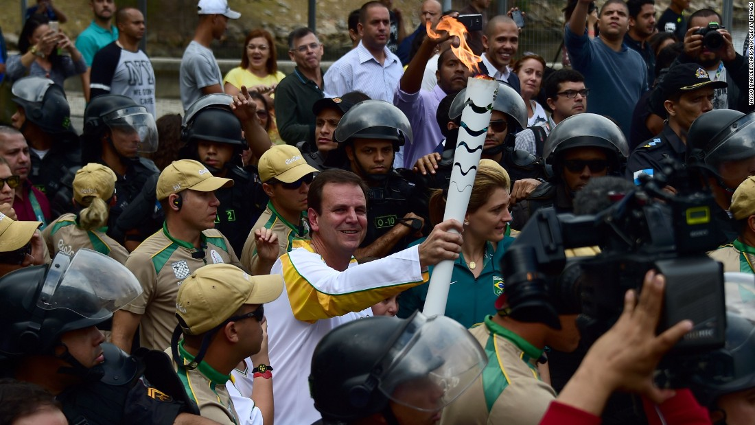 Rio mayor Eduardo Paes carries the Olympic torch after its arrival at the Naval Academy on Guanabara Bay, ahead of Friday's opening ceremony.