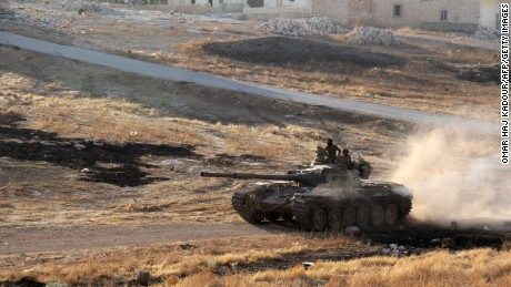 Opposition fighters drive a tank in the Al-Huweiz area on the southern fringe of Aleppo on August 2, 2016.