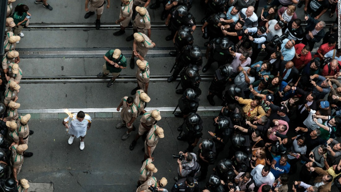 An Olympic torch bearer runs past the crowds held back by lines of security. National force police reportedly used tear gas and rubber bullets against protesters along the torch route Wednesday.