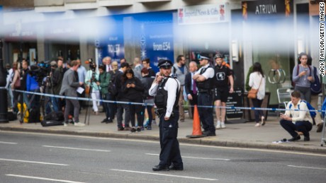 Journalists and others gather as police guard the attack scene Thursday in London's Russell Square.