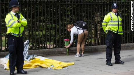 A woman lays flowers at the scene of the knife attack in Russell Square in London, on Thursday, August 4.