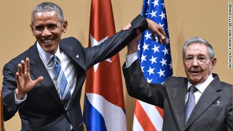 "Cuban President Raul Castro (R) raises US President Barack Obama's hand during a meeting at the Revolution Palace in Havana on March 21, 2016. Cuba's Communist President Raul Castro on Monday stood next to Barack Obama and hailed his opposition to a long-standing economic ""blockade,"" but said it would need to end before ties are fully normalized."