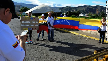 "Venezuelans pose with Venezuelan and Colombian flags and a sign reading ""Colombia thank you for your solidarity with Venezuela"" in San Antonio del Tachira, Venezuela as they prepare to cross the border with Colombia on July 10, 2016.  Thousands of Venezuelans crossed Sunday the border with Colombia to take advantage of its 12-hour opening after it was closed by the Venezuelan government 11 months ago. Venezuelans rushed to Cucuta to buy food and medicines which are scarce in their country. / AFP / GEORGE CASTELLANOS        (Photo credit should read GEORGE CASTELLANOS/AFP/Getty Images)"