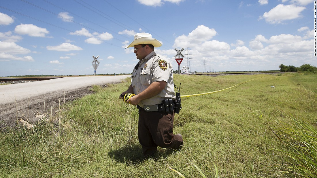 "Caldwell County Sheriff's Deputy Sean Quinn rolls out crime-scene tape to secure the scene of a <a href=""http://www.cnn.com/2016/07/30/us/texas-hot-air-balloon-crash/"" target=""_blank"">hot-air balloon crash</a> near Lockhart, Texas, on Saturday, July 30. Sixteen people were killed."