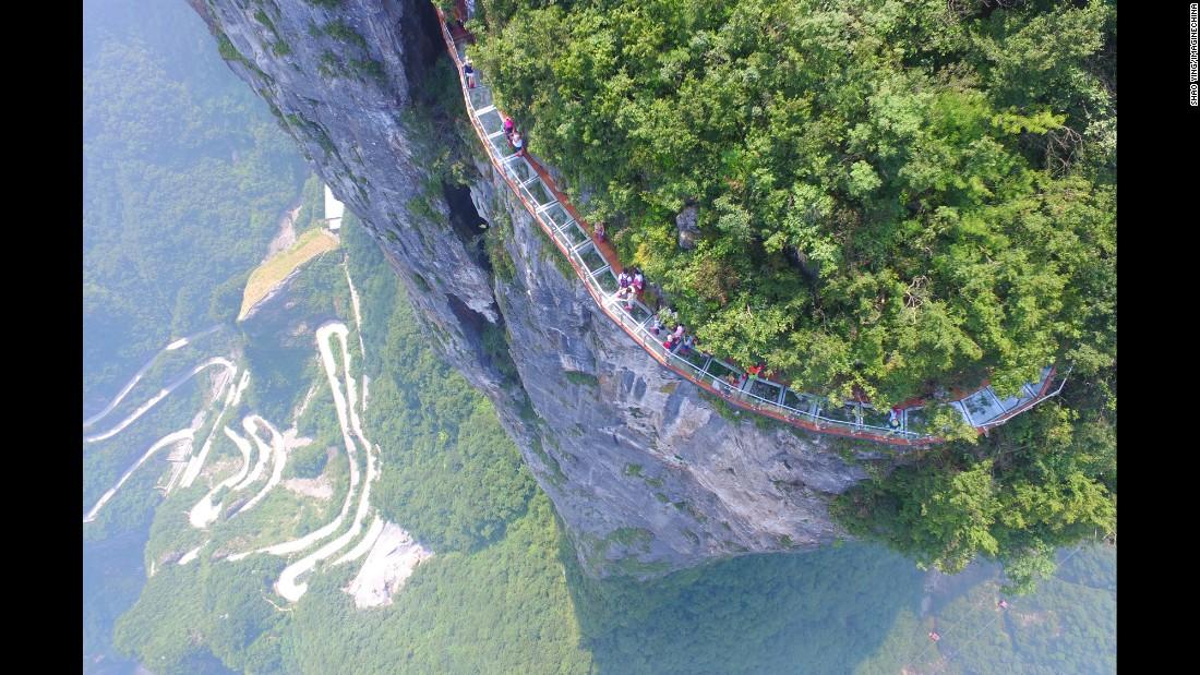 "People walk on <a href=""http://www.cnn.com/2016/08/02/travel/china-tianmen-mountain-glass-skywalk/"" target=""_blank"">a new glass skywalk</a> Monday, August 1, on Tianmen Mountain in Zhangjiajie, China."