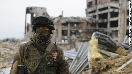 An armed pro-Russian separatist of the self-proclaimed Donetsk People's Republic (DNR) stands in front of the destroyed Donetsk International Airport, in Donetsk.