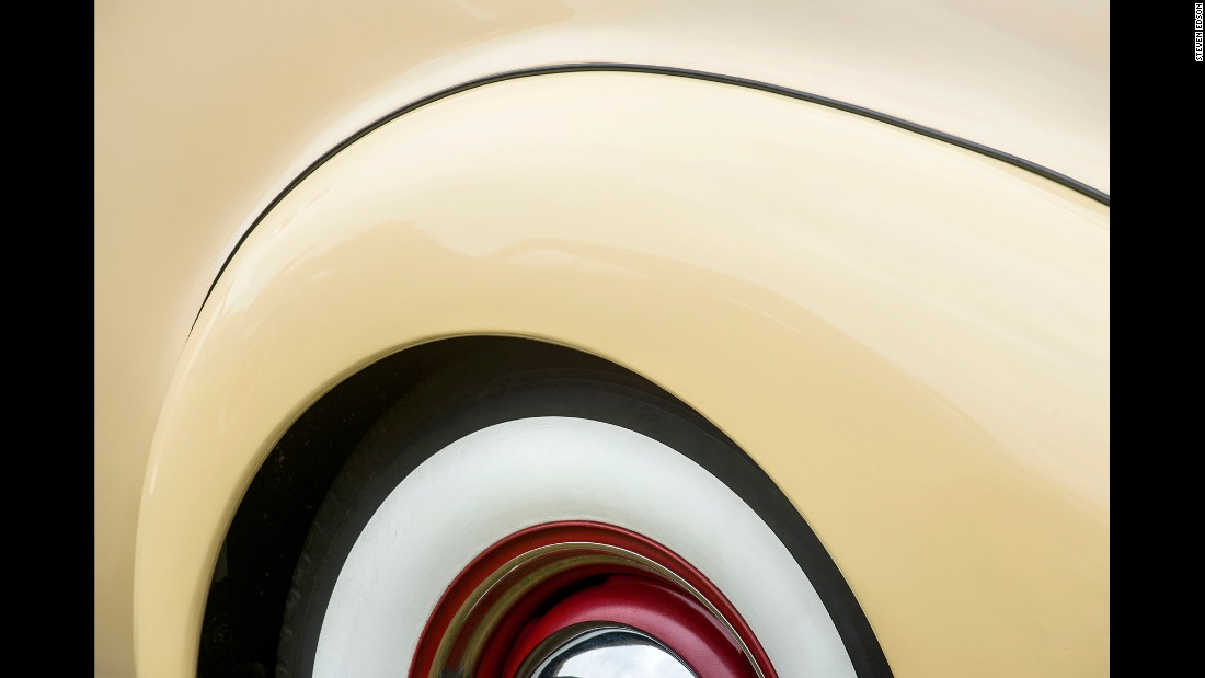A rear quarter of a 1938 Packard Opera Coup, including part of the white wall tire, red wheel and hubcap