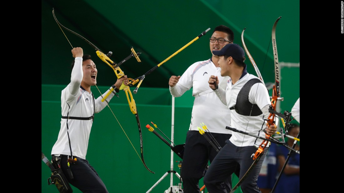 South Korea's Ku Bon-chan, Kim Woo-jin and Lee Seung-yun celebrate after winning the men's team archery gold medal match at the Sambadrome venue.