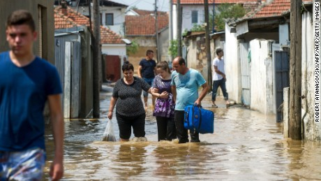 People wade through floodwaters on Sunday in the village of Stajkovci, near Skopje, Macedonia.