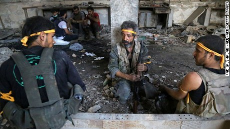 Rebel fighters rest during clashes with regime forces in Al Ramouseh on Aleppo's southwestern fringe Saturday.